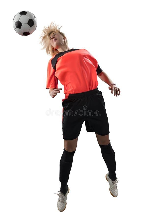 Footballeur féminin sautant pour la boule d'isolement photo stock