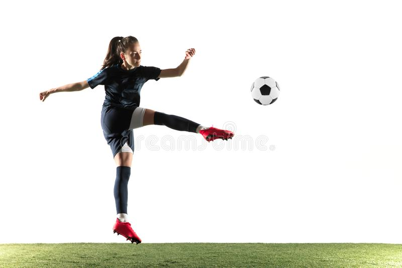 Footballeur f?minin donnant un coup de pied la boule d'isolement au-dessus du fond blanc photographie stock libre de droits