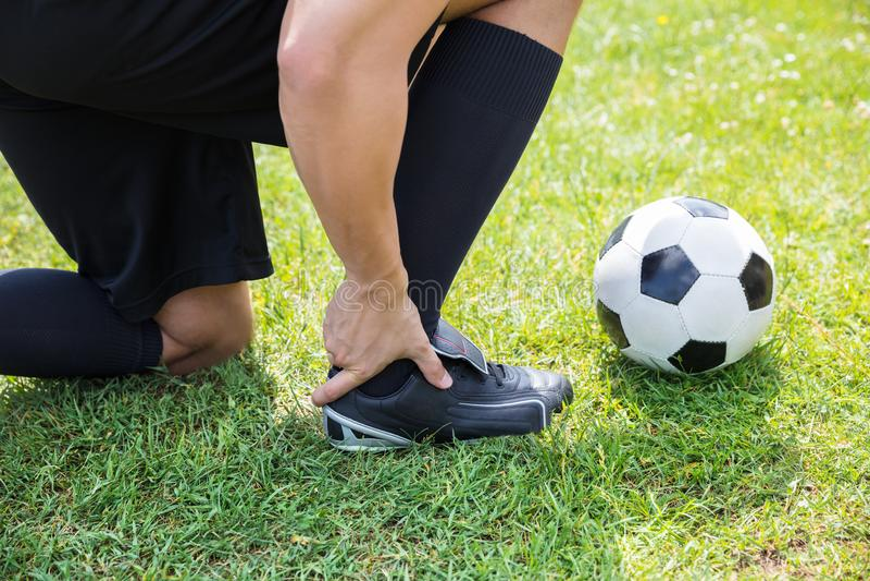 Footballeur masculin souffrant de la blessure à la cheville photo libre de droits