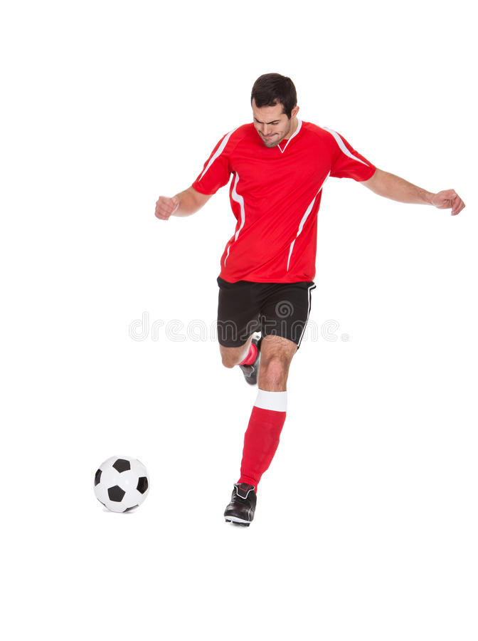 Footballeur professionnel donnant un coup de pied la bille photo libre de droits