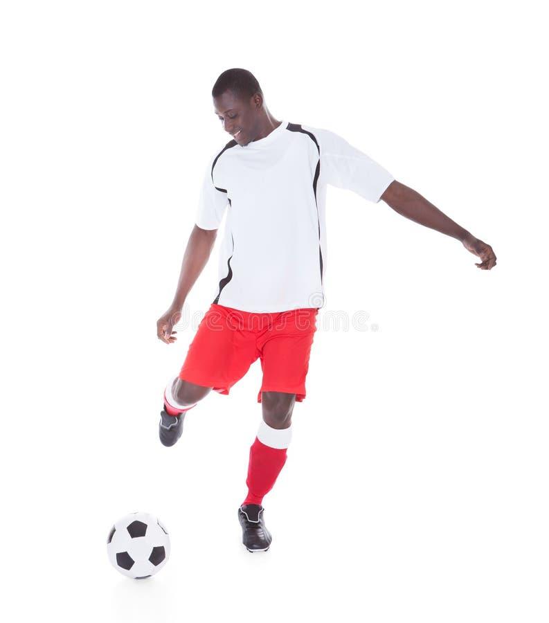 Footballeur professionnel donnant un coup de pied la boule photos stock