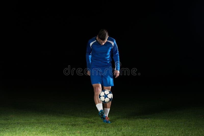 Footballeur professionnel donnant un coup de pied la boule d'isolement sur le noir images stock