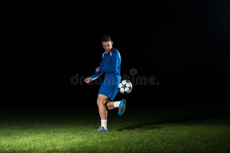 Footballeur professionnel donnant un coup de pied la boule d'isolement sur le noir photos stock