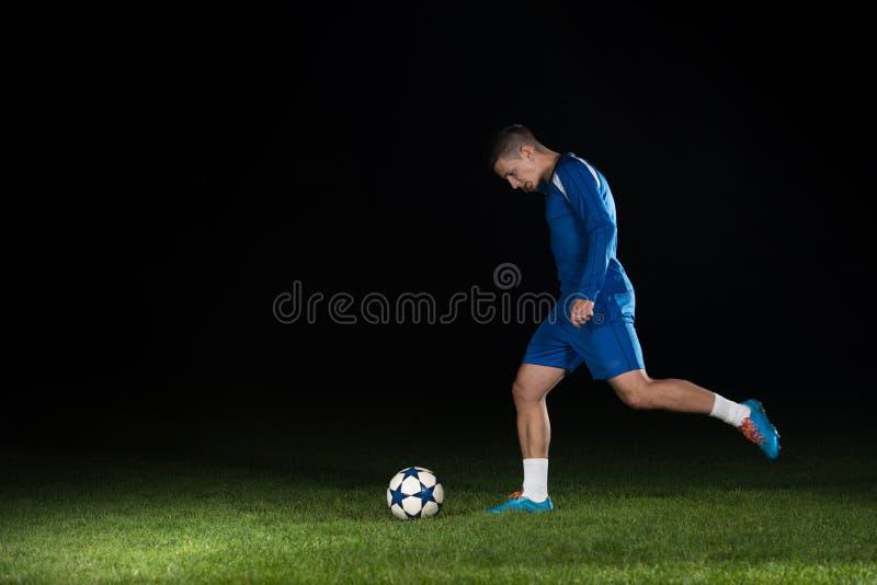 Footballeur professionnel donnant un coup de pied la boule sur le noir photos libres de droits