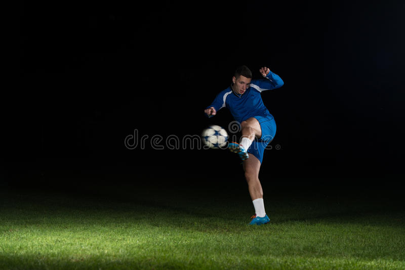 Footballeur professionnel donnant un coup de pied la boule sur le noir images stock