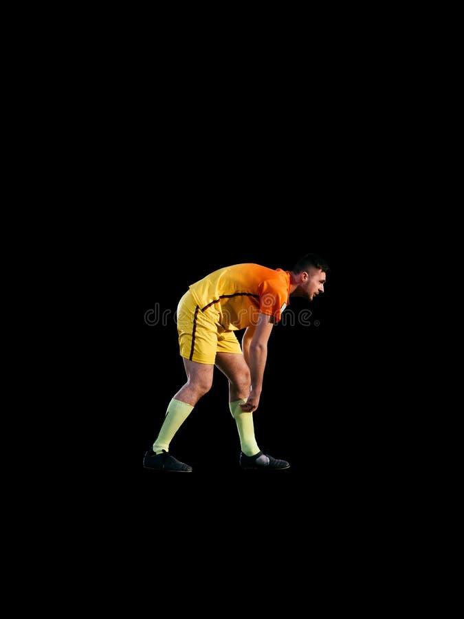 Footballeur professionnel jouant sur le fond noir photos libres de droits