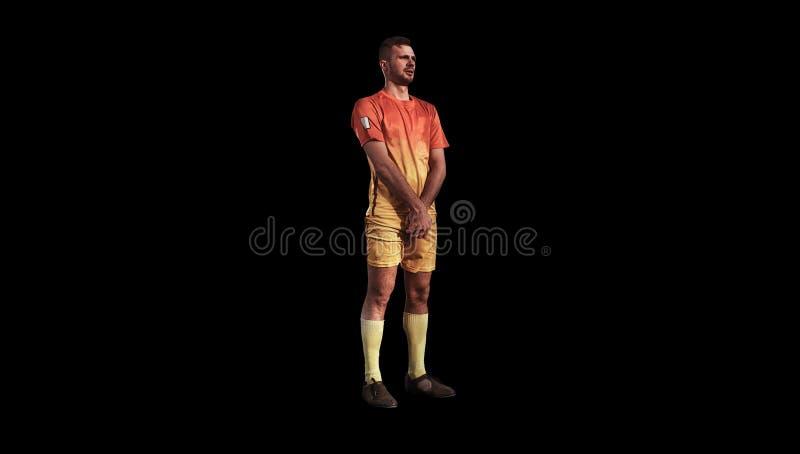 Footballeur se tenant sur le fond noir image libre de droits