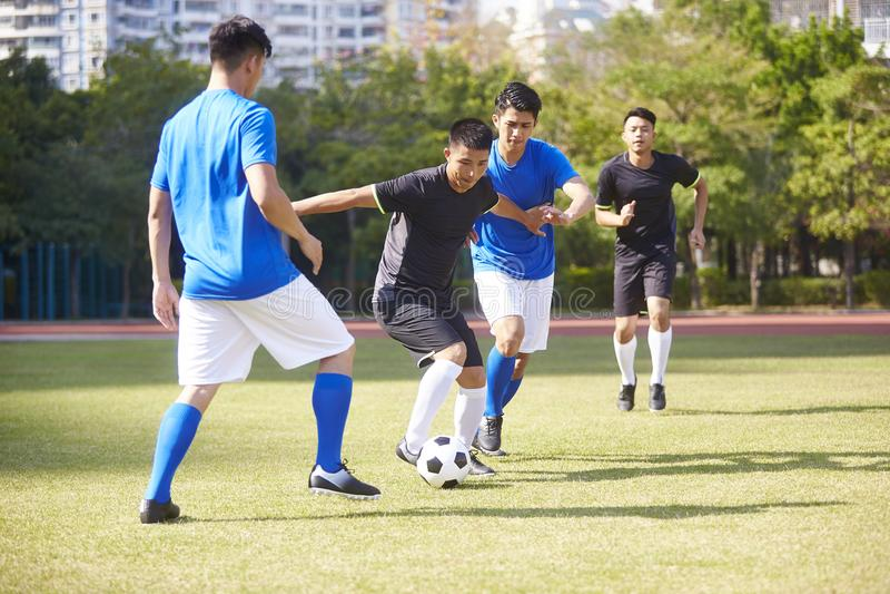 Footballeurs asiatiques jouant sur le champ photographie stock libre de droits
