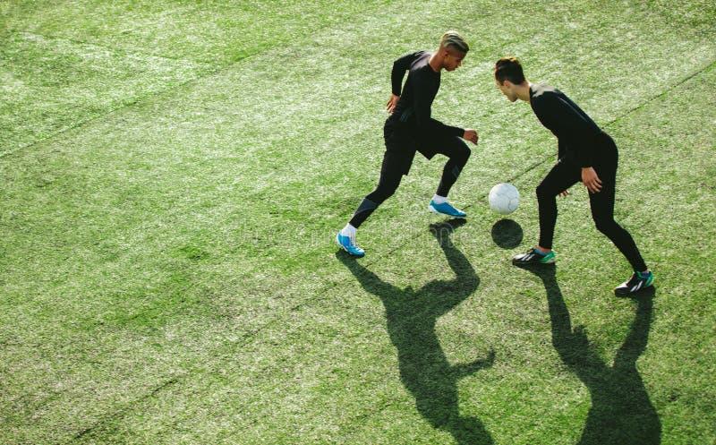 Footballeurs dans l'action sur le champ photographie stock