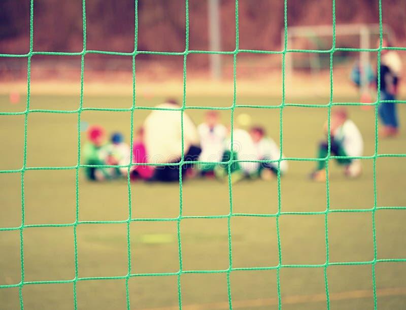 Footballists und Stadionsarenafußballplatz defocused Vew durch Fußballnetz stockfoto