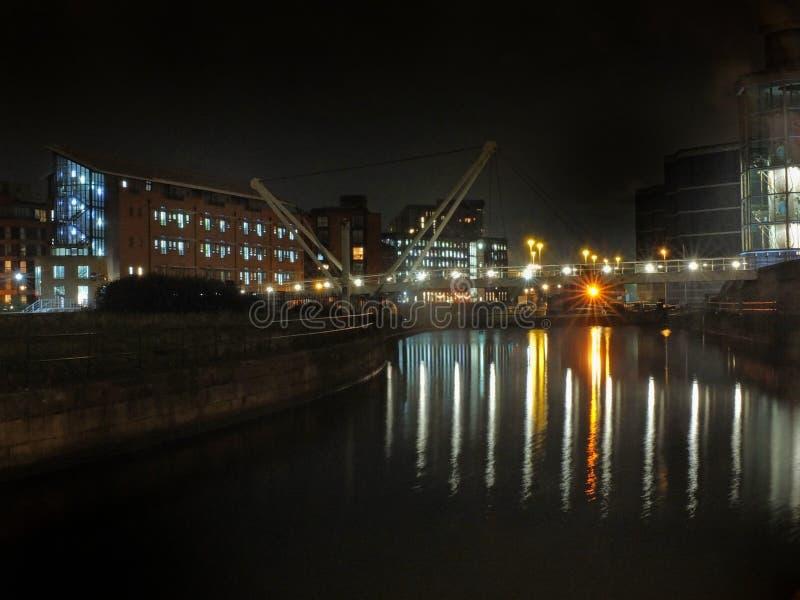 Footbridge пути рыцарей пересекая River Aire на вход замка к доку clarence в Лидсе вечером со зданиями и светами стоковые фотографии rf