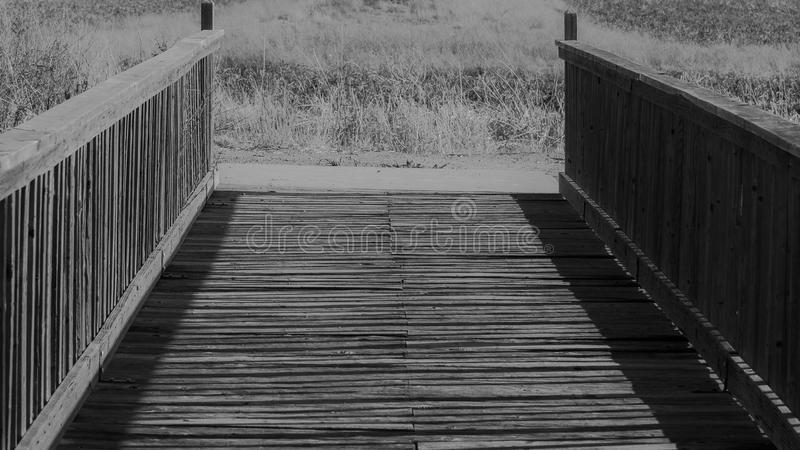 Footbridge in black and white. Late afternoon sun highlights the slat construction of the side rails of this footbridge at Whitewater Draw in southeast Arizona royalty free stock image