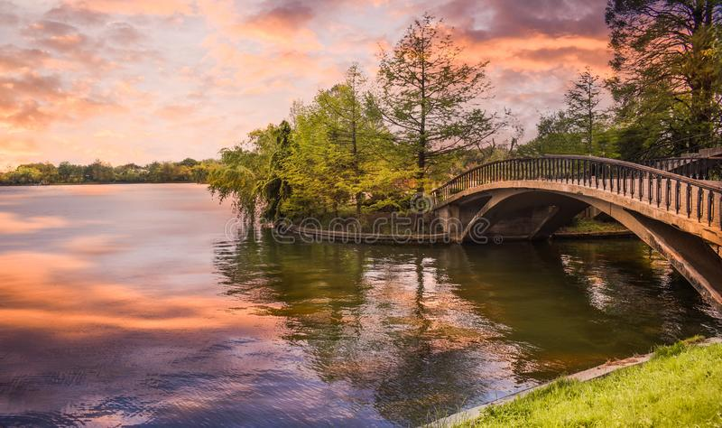 Footbridge over the pond in the city park at sunset. Styled stock photo with wooden bridge in twilight atmosphere in Herastrau. Park from Bucharest. Romanian royalty free stock images