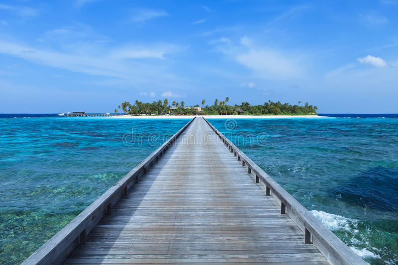 Footbridge over turquoise ocean to Island royalty free stock images