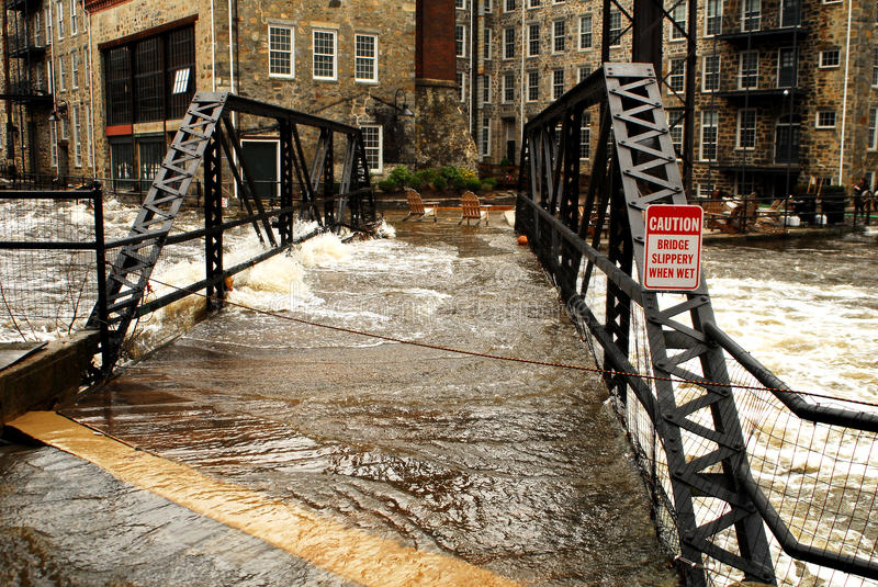 Footbridge overcome by flood. The pedestrian footbridge at the Royal Mills Complex in West Warwick, Rhode Island is overtaken by flood waters from the raging royalty free stock image