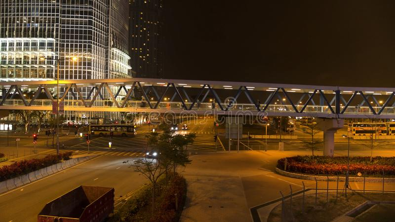 Footbridge with passersby above the road on night city background. Stock. Pedestrian bridge with people walking on night royalty free stock photography