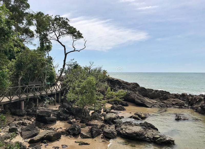 Footbridge passing over the rocks by the ocean royalty free stock photo