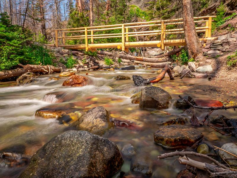 Footbridge to Cross Over Baring Creek in GNP. The image of Baring Creek and the footbridge that leads to Baring Falls in GNP royalty free stock photography