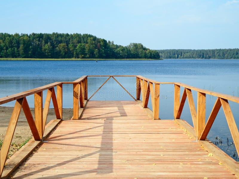 Footbridge. Wooden footbridge on the shore of the lake stock images