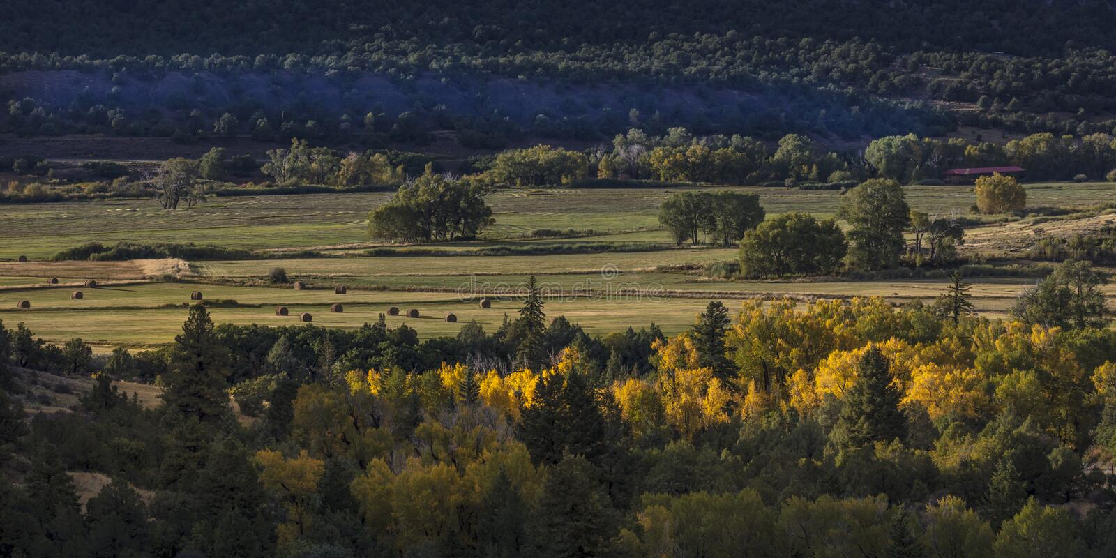 Foothills of San Juan Mountains in Autumn with hay bails in dist stock photography