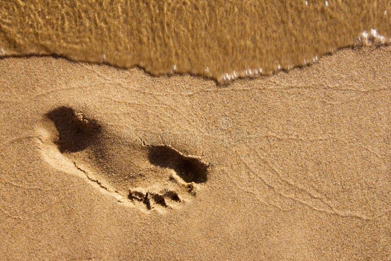 Footmark op nat verzendt stock foto