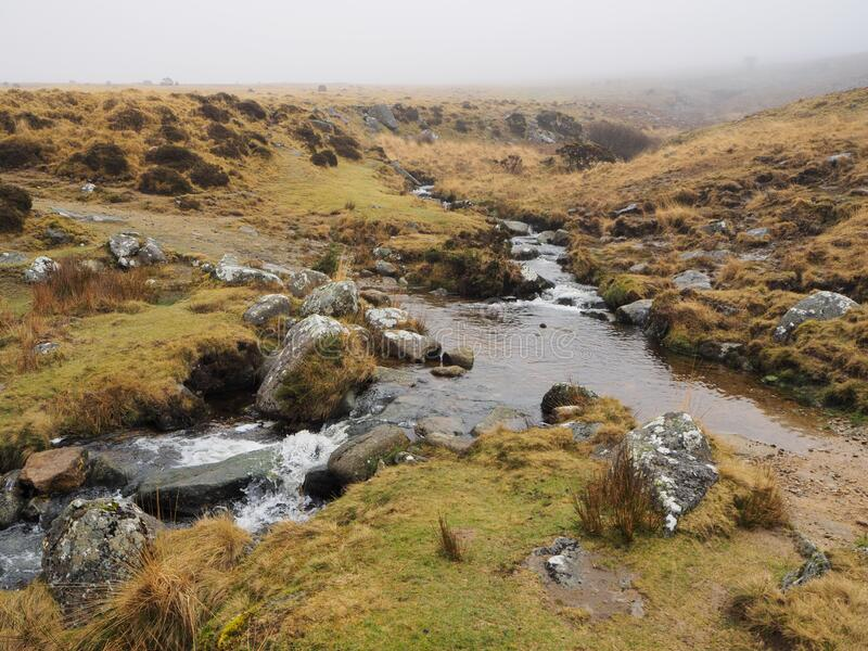 Footpath across Red-a-ven Brook as it cascades over rocks below mist and low cloud, Dartmoor National Park, Devon stock photo