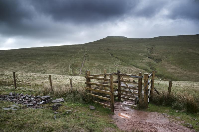 Footpath in Brecon Beacons landscape leading to Corn Du peak wit. H stormy sky overhead royalty free stock photos