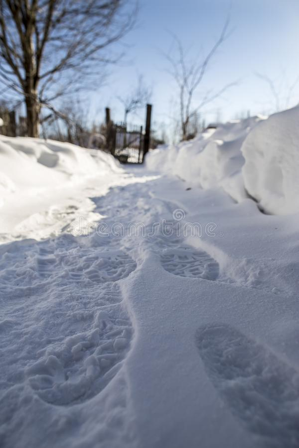 A footpath cleared of snow with footprints leads to an old rickety wicket and a fence among snowdrifts, against a blue sky on a stock photo