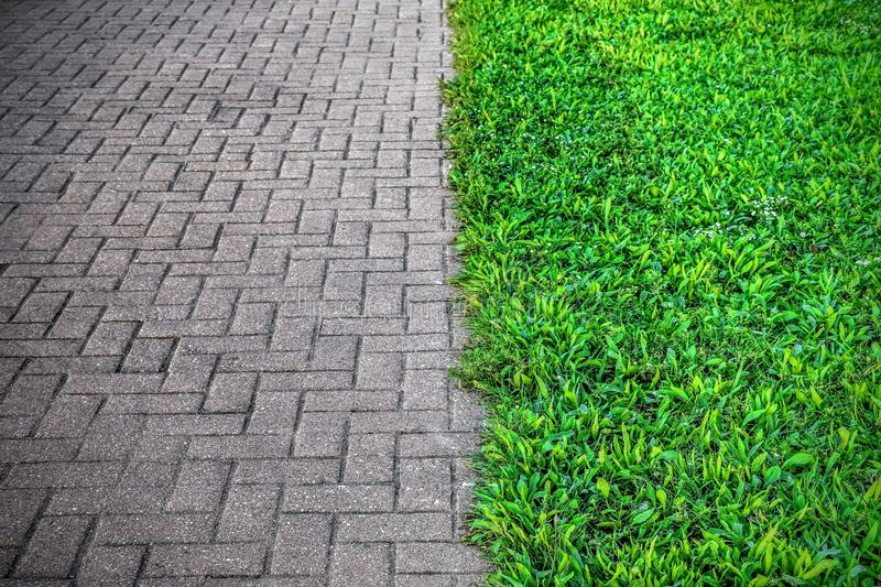 A FOOTPATH AND GRASS WITH SPLIT TONE. ARTISTIC VIEW IN COLOR DIFFERENCE BETWEEN A FOOTPATH TILES AND GRASS NEAR IT stock photography
