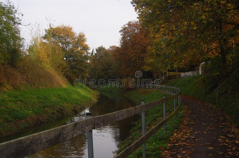 Footpath next to creek in autumn. royalty free stock photo
