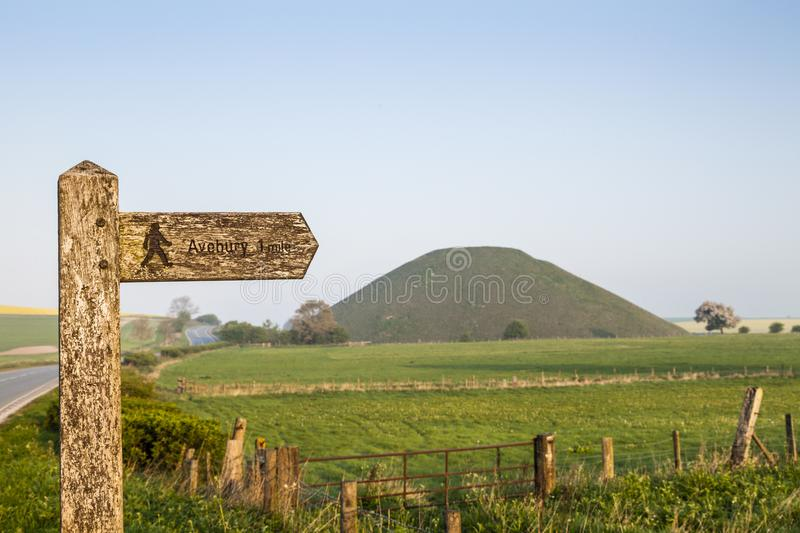 Footpath Signpost to Avebury, Near Silbury Hill. Signpost for footpath to Avebury in Wiltshire, with Silbury Hill, a Neolithic monument, in background. Avebury stock photo