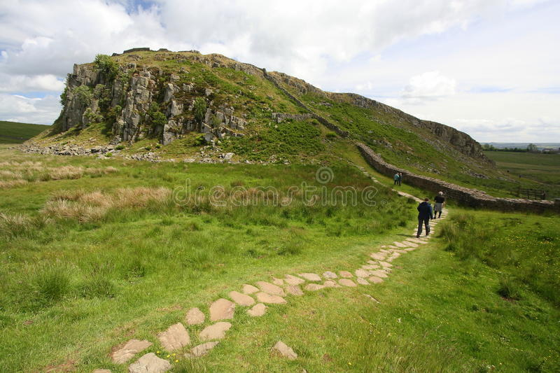 Footpath and walkers alongside Hadrian`s Wall. Footpath and walkers alongside the Roman built Hadrian`s Wall, which crosses over Crag Lough in Northumberland in stock images