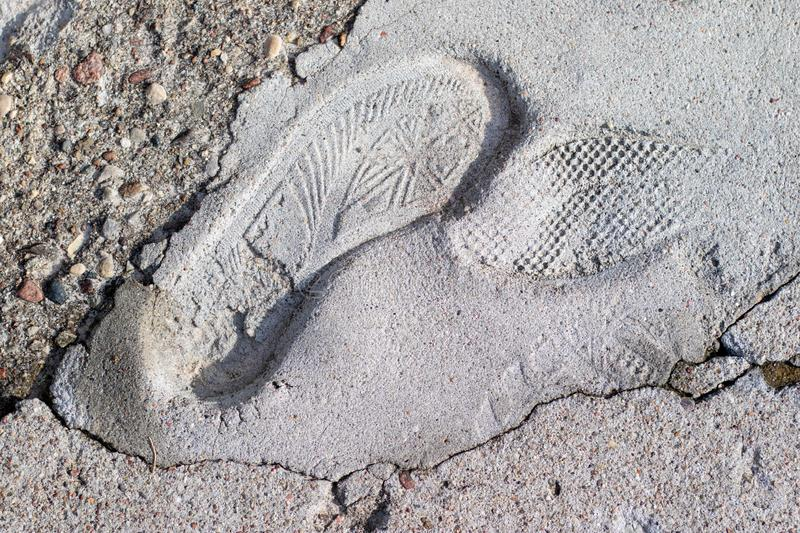 The footprint of a sports shoe imprinted in concrete. An imprint royalty free stock photo