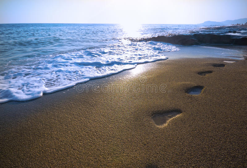Footprints on the beach. And sunset royalty free stock photography