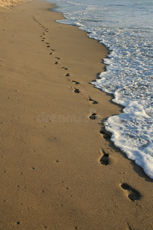 Footprints on the beach. Being washed away by the waves royalty free stock images
