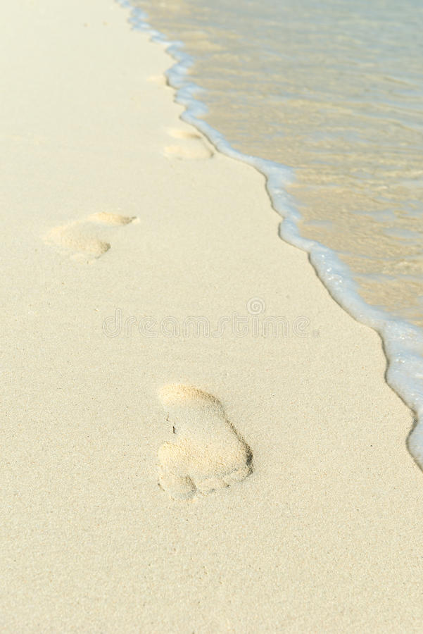Footprints on the beach. Footprints on a beach with white sand stock photo