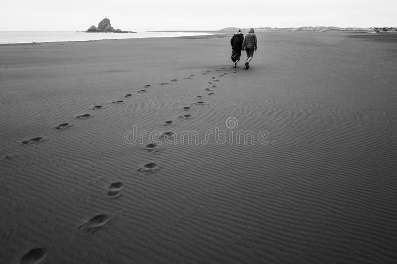 Footprints on the Beach / Couple / Piha, New Zealand. On a windy day at Piha Beach I saw this couple enjoying the silent and lonely Beach. The black sand had an royalty free stock photography