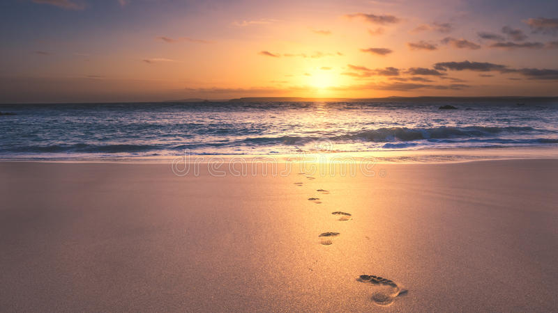 Footprints on the beach. At sunrise in cornwall stock photography