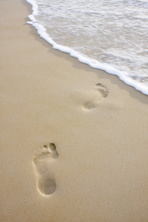Footprints on beach and wave stock photography