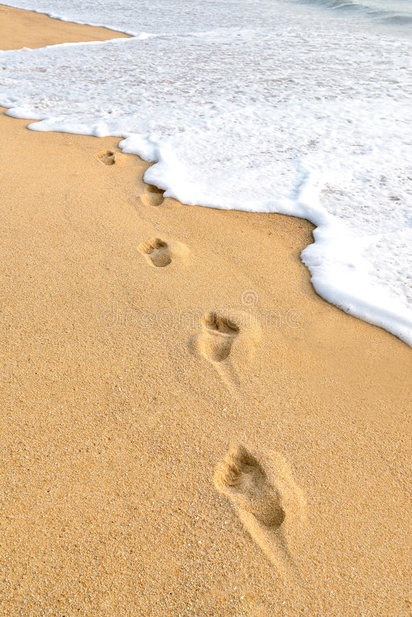 Footprints on beach. Footprints on the beach with a wave in sunset royalty free stock photo