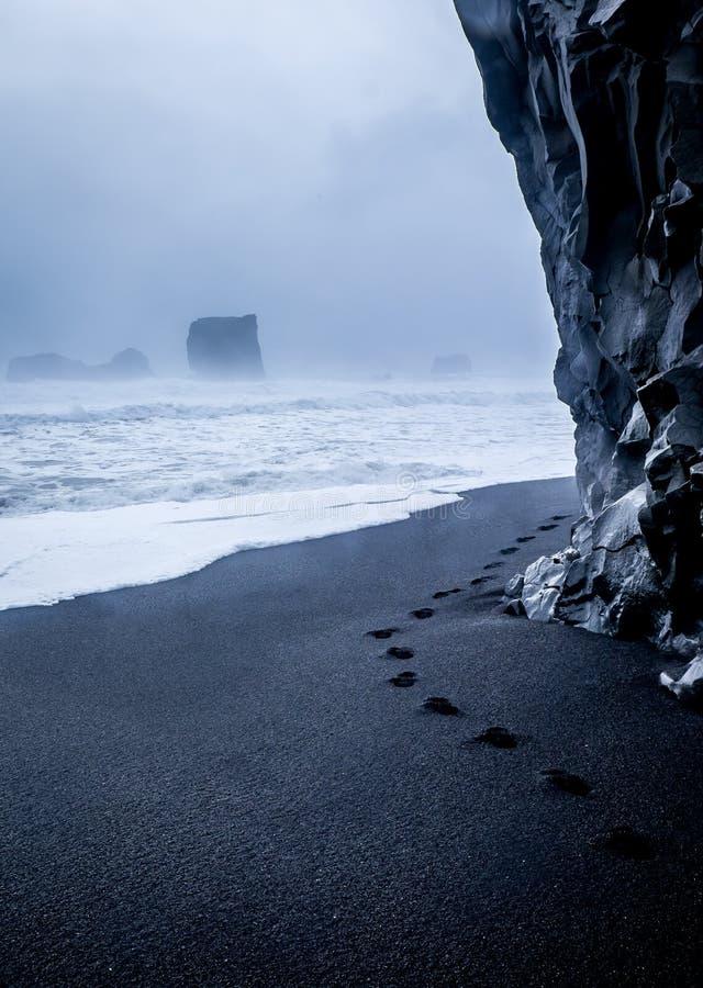 Footprints on black sand, Icelandic beach royalty free stock photography
