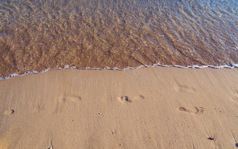 Footprints on a empty sandy beach - small waves approaching royalty free stock photography