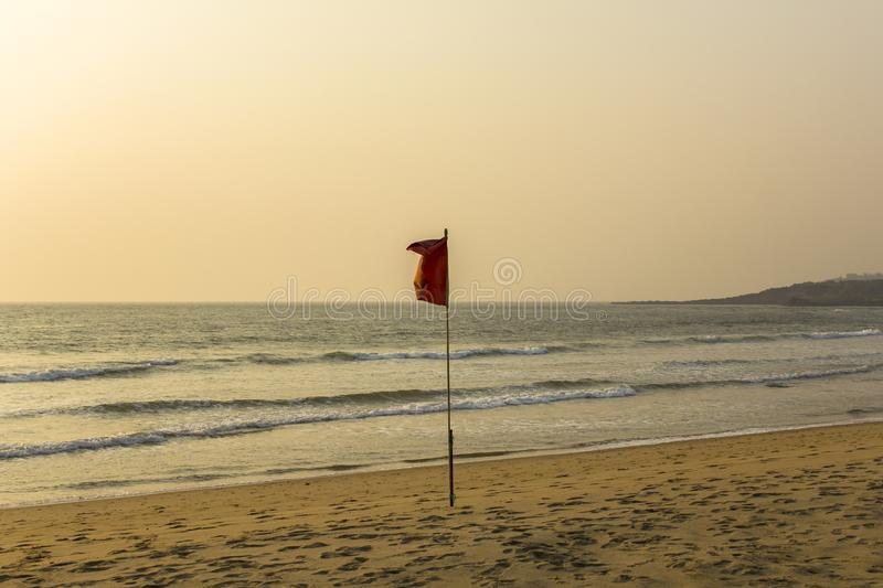 Footprints of people on a yellow sandy beach near a red flag prohibiting swimming against the backdrop of sea waves under a clear. A footprints of people on a royalty free stock image