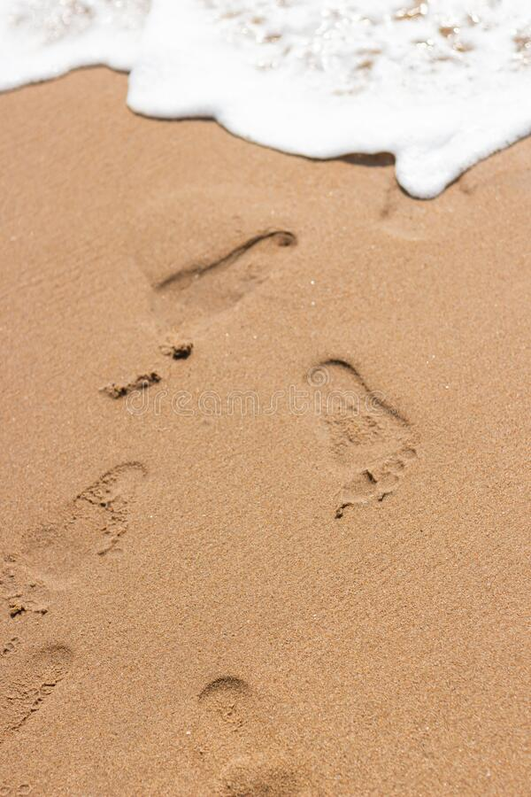 Footprints on the sand of the beach. And white color of sea wave bubble royalty free stock photos