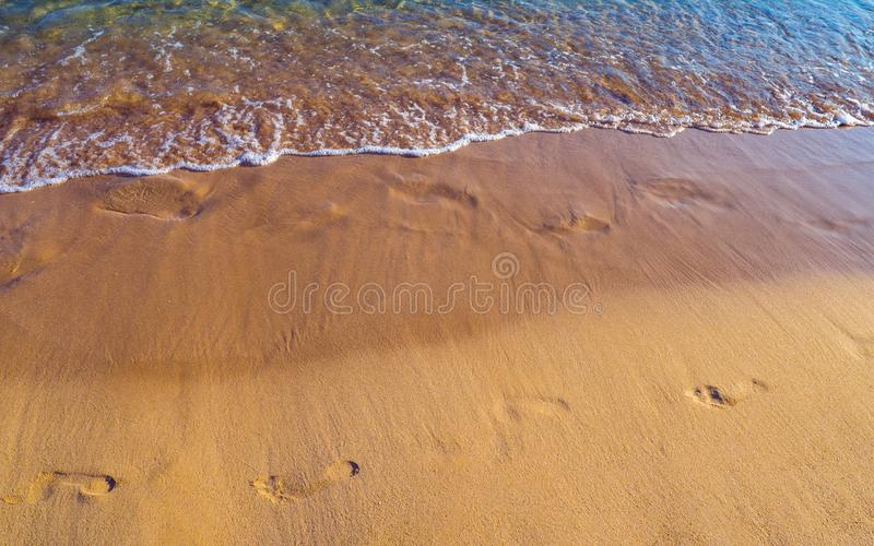 Footprints in the sand on the empty sandy beach - small foamy wave and clear blue water stock images