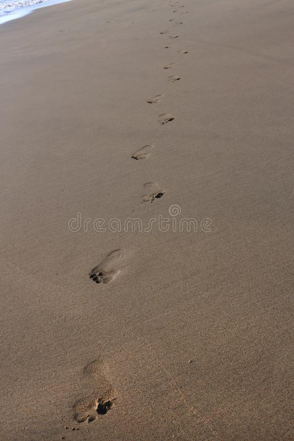 Footprints on the Sand in Jimbaran Beach, Bali. Footprints of an adult human on a sand of Jimbaran Beach in Bali, Indonesia. Wonderful and inspiring travel photo stock photo