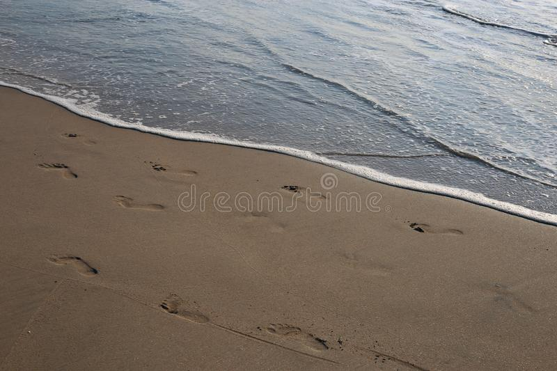 Footprints on the Sand in Jimbaran Beach, Bali. Footprints of an adult human on a sand of Jimbaran Beach in Bali, Indonesia. Wonderful and inspiring travel photo stock images