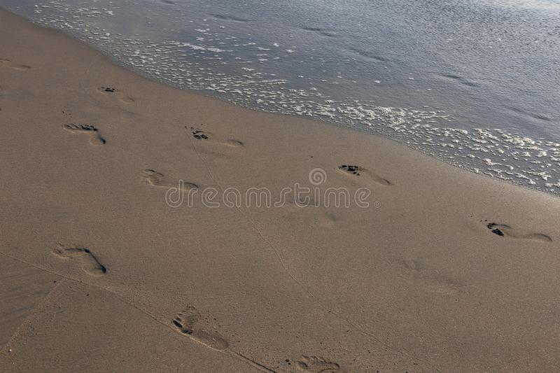 Footprints on the Sand in Jimbaran Beach, Bali. Footprints of an adult human on a sand of Jimbaran Beach in Bali, Indonesia. Wonderful and inspiring travel photo royalty free stock photos