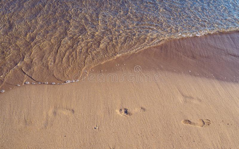 Footprints in the sand with small wave approaching stock photography