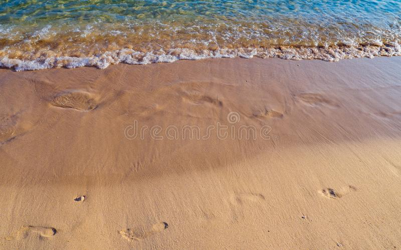Footprints on the sandy beach being washed away royalty free stock photos